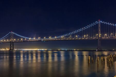 Photo pour San Francisco Bay Bridge on a clear night, lit up by yellow and blue lights, reflecting of the water in the Bay, long exposure - image libre de droit