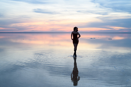 Photo pour Salt lake. Girl standing in the water at sunset. The reflection in the water. - image libre de droit