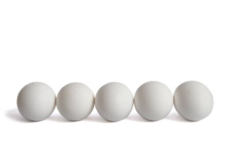 Five white chicken eggs lie scarcely