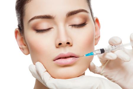 Foto de Closeup of beautiful woman gets injection in her lips. Isolated over white background - Imagen libre de derechos