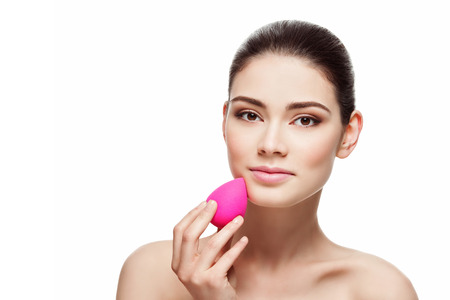 Photo pour Beautiful young woman applying makeup using beauty blender sponge. Isolated over white background - image libre de droit
