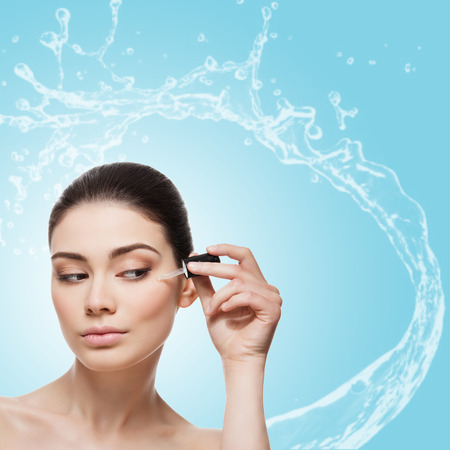 Beautiful young woman applying anti-ageing moisturizing serum to under eye area. Isolated over light blue background with water splash. Square composition. Copy space.