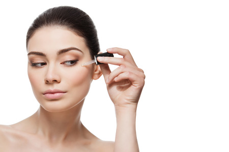 Beautiful young woman applying anti-ageing moisturizing serum to under eye area. Isolated over white background. Copy space.