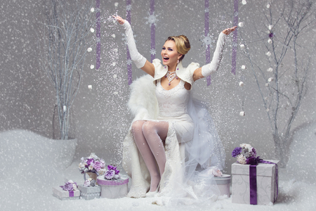 Beautiful happy young bride in felted wedding gown throwing up snow. Present boxes decorated with purple flowers.