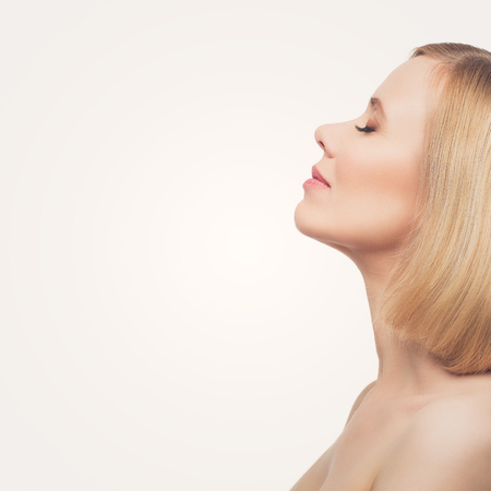 Photo pour Profile of beautiful middle aged woman with smooth skin and short blond hair. Beauty shot. Isolated over white background. Copy space. - image libre de droit