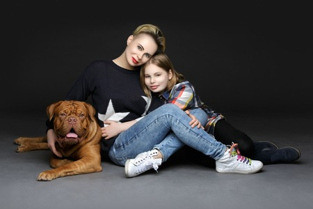 Mother and daughter in casual clothes with big brown dogue de bordeux dog over black background. People with pet.