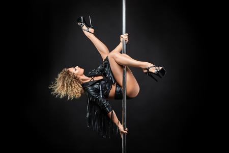 Photo pour beautiful pole dancer in leather jacket on pylon - image libre de droit