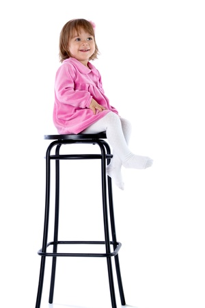 Photo pour The little girl sits on a high chair. Isolated on a white background - image libre de droit