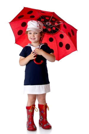 The little girl with an umbrella and in rubber boots. Isolated on a white backgroundの写真素材