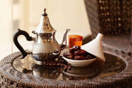 Photo pour A metal teapot, a glass with a drink, dates and an Arabic rosary lie on the table. Ramadan Kareem. festive still life - image libre de droit