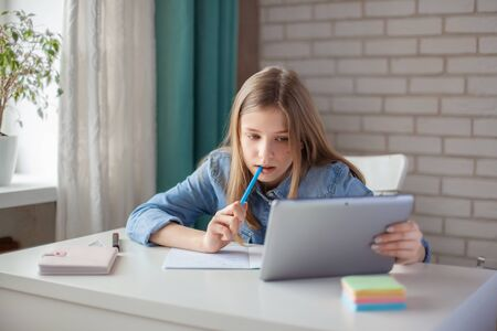 Photo pour A cute girl does her homework using a tablet during self-isolation, while the school is closed for quarantine. Social distance, online learning, distance learning - image libre de droit