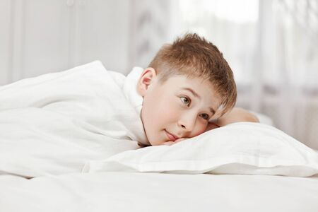 Photo pour A cute teenage boy is lying on the bed in the bedroom. Close-up, space for text - image libre de droit