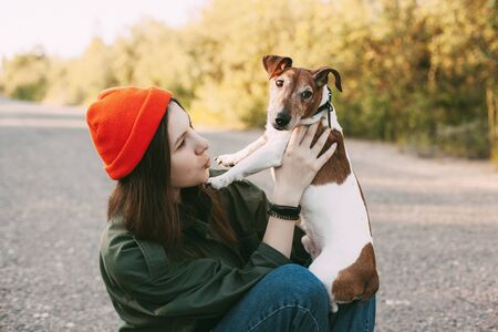 Photo pour A beautiful girl in an orange hat holds her dog in her arms. The girl takes care of her pet and walks with him in the fresh air. Pet, friend, friendship, care - image libre de droit