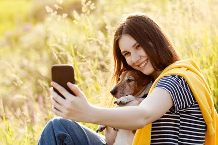 Photo for An attractive teen girl takes photos of herself and her dog using a mobile phone camera. A girl takes a photo while walking with her pet, space fot text - Royalty Free Image