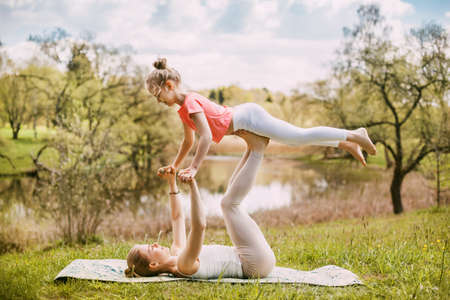 Photo pour A young mother and daughter in sportswear do yoga together in a Park. The concept of a family holiday. Sports, fitness, meditation - image libre de droit