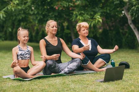 Photo pour Grandmother, mom and child meditate together in nature. Go in for sports. Healthy lifestyle - image libre de droit