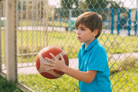Foto per A cute boy in a blue t-shirt is holding an orange basketball. The athlete is resting during the game. The concept of a healthy lifestyle - Immagine Royalty Free