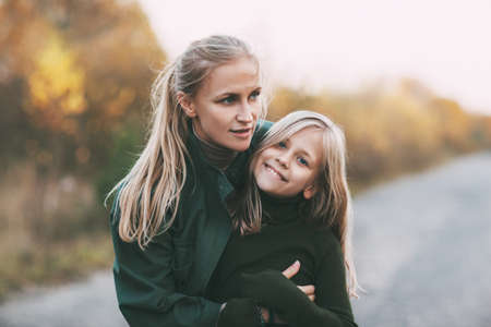 Photo for Portrait of happy mature mom and her blonde little daughter hugging and laughing while walking in autumn park outdoors. - Royalty Free Image