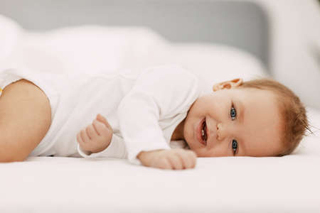 Photo pour A blue-eyed baby lies in a snow-white bed under a blanket, laughs and indulges - image libre de droit