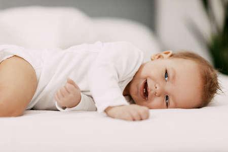Foto für A blue-eyed baby lies in a snow-white bed under a blanket, laughs and indulges - Lizenzfreies Bild