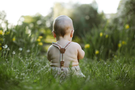 Photo pour small baby boy sitting in the grass - image libre de droit