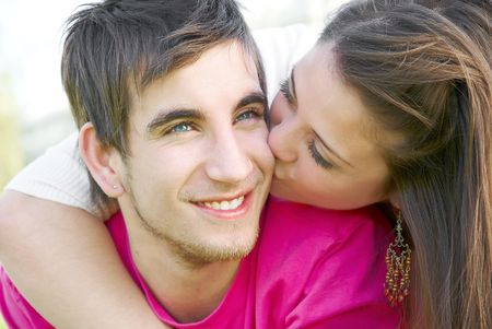 Young happy attractive couple kissing outdoors