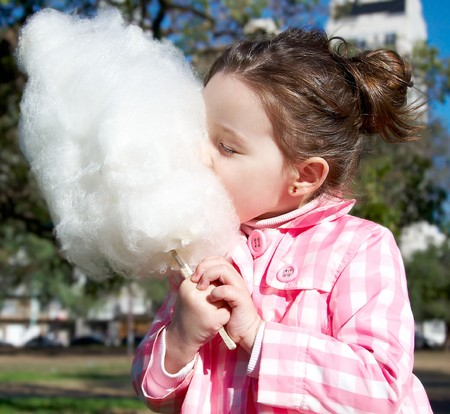 Cute girl eating candy-floss in the park