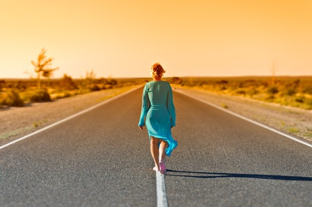 Women walking far away on rural road in summer day