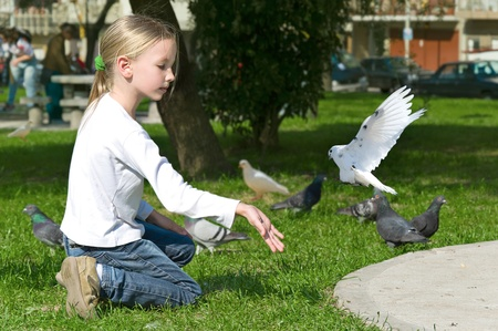Happy laughing little girl feeding Pigeons in the park