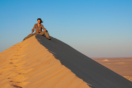 Foto de Young woman in khaki clothes sitting on a huge sand dune in Sahara desert - Imagen libre de derechos