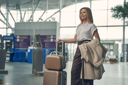 Photo pour Cheerful female person standing near her suitcase - image libre de droit