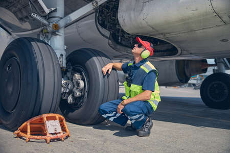 Photo for Qualified young technician inspecting the undercarriage axle - Royalty Free Image