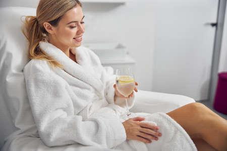 Photo pour Joyful young woman with drink relaxing in spa salon - image libre de droit