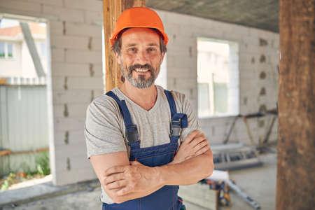 Photo pour Joyful mature builder inside a half-finished house - image libre de droit