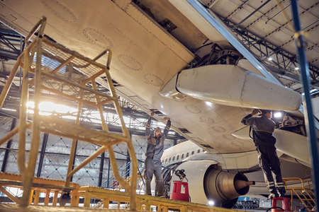 Photo pour Men mechanics repairing of wing and engine of the aircraft in the hangar - image libre de droit