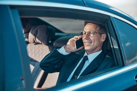 Photo for Cheerful businessman talking on smartphone during transfer from airport - Royalty Free Image