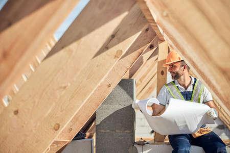 Photo pour Contented man holding a blueprint of a new building - image libre de droit