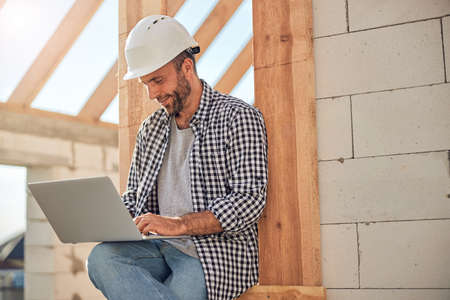 Photo pour Ambitious field engineer working on his laptop near a building - image libre de droit
