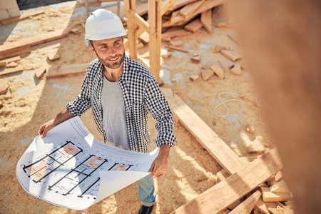 Photo pour Qualified construction site worker with a blueprint of a house - image libre de droit