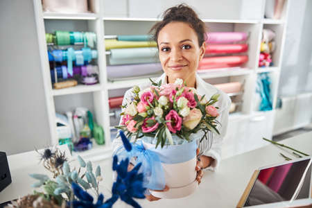 Photo for Beautiful female florist holding a pot with roses - Royalty Free Image