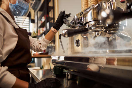 Photo pour Woman waiter cleaning coffee machine in the cafe bar - image libre de droit
