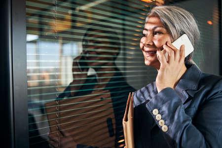 Photo pour Cheerful woman talking on cellphone at work - image libre de droit