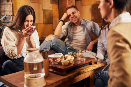 Photo for Charming young woman enjoying tea with friends in cafe - Royalty Free Image