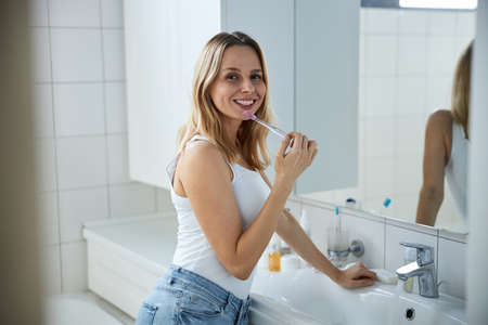 Photo pour Beautiful young woman brushing teeth at home - image libre de droit