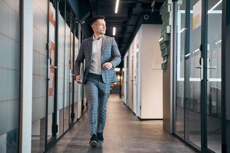 Photo pour Stylish young man walking down the hallway - image libre de droit
