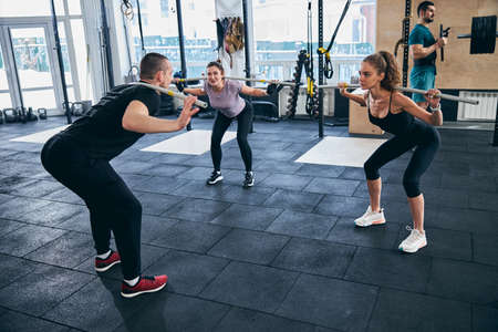 Photo for Fitness instructor and his female clients working out together - Royalty Free Image