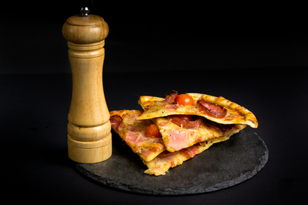 pizza slices on a black background with a pile and a mill for sp