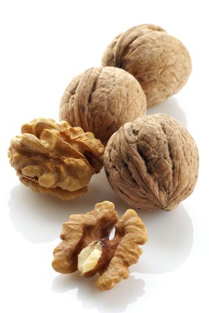 Whole and hulled walnuts on white background.