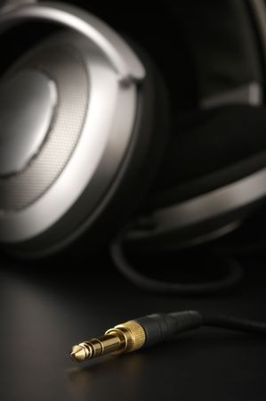 Close-up of gilded jack against silver headphones. Selective focus on top of jack.
