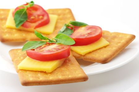 Three square crackers with slices of cheese, tomato and basil in white plate on white background.